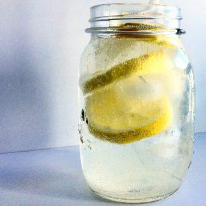 a jar filled with lemon soda and lemons
